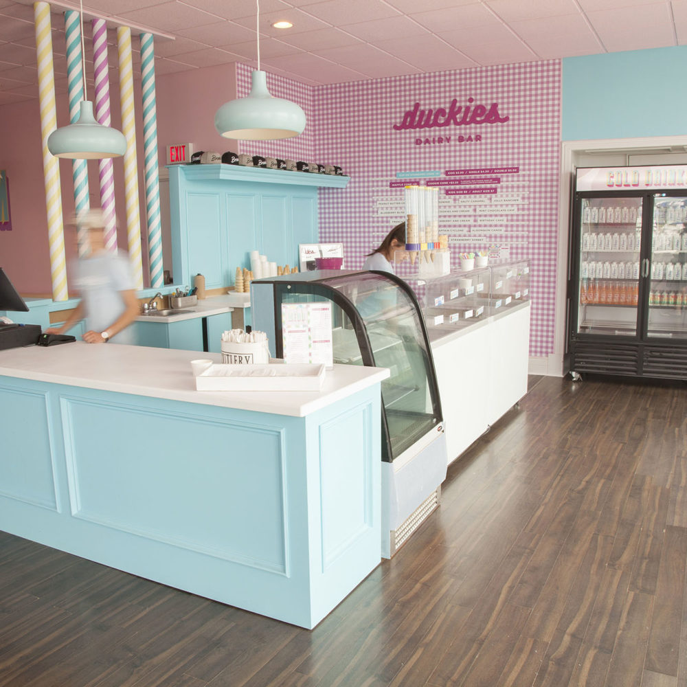 Interior of Duckies Dairy Bar with counter and cash register, and refrigerator with cold drinks.