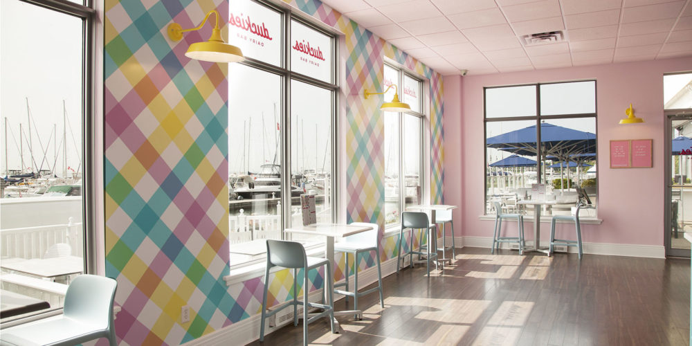 Interior of Duckies Dairy Bar with tables and chairs in front of large windows.