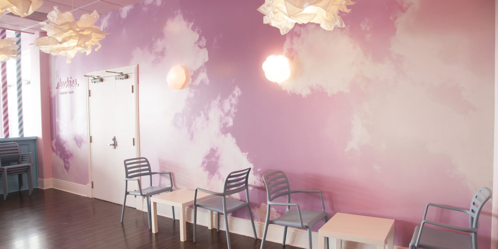 Interior of Duckies Dairy Bar with tables and chairs in front of a mural with pink clouds.